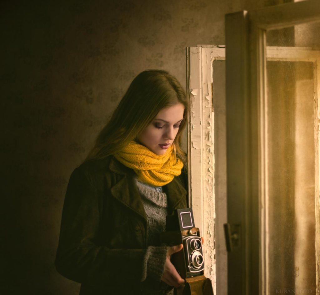 Eine Frau steht am Fenster und schaut auf ihre Kamera