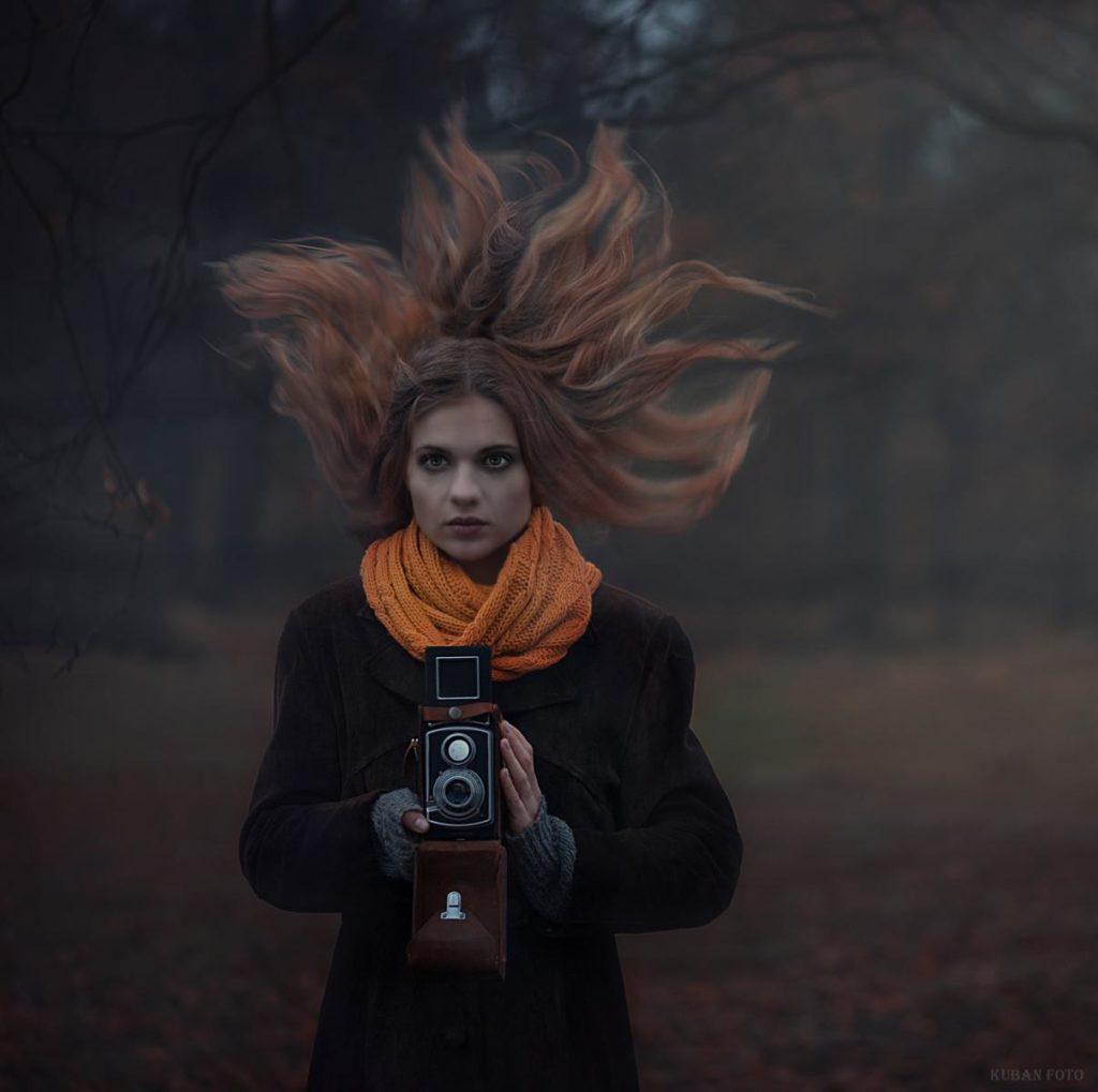 Eine junge Frau hält eine alte Kamera in der Hand