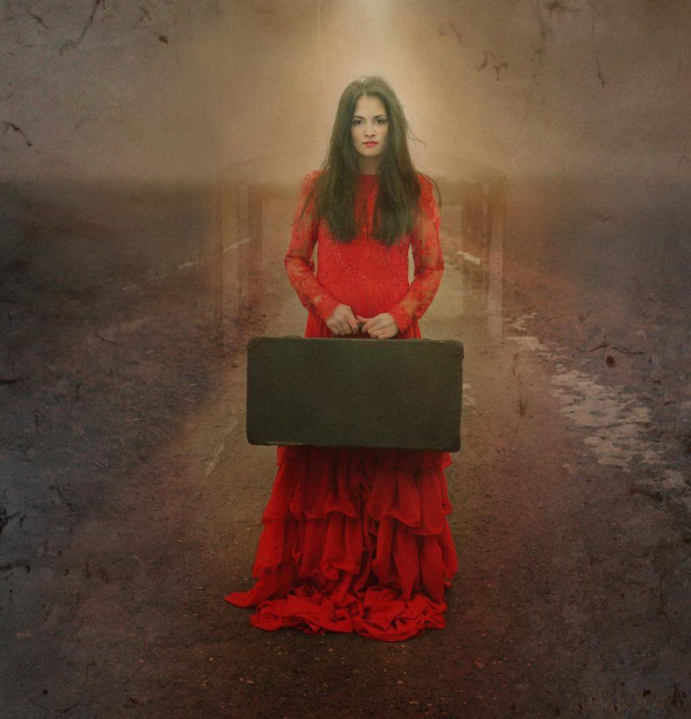 Eine Frau im roten Kleid mit alten Koffer