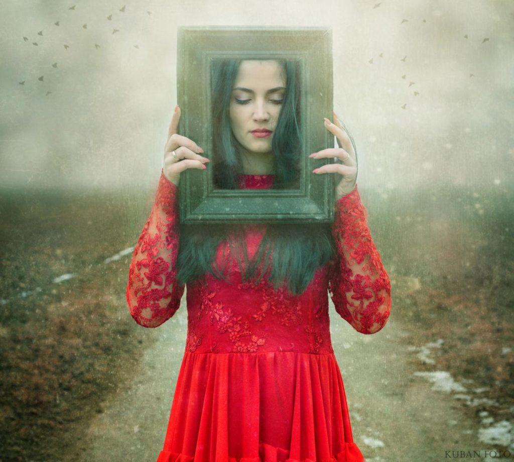Eine Frau im roten Kleid mit altem Bilderrahmen