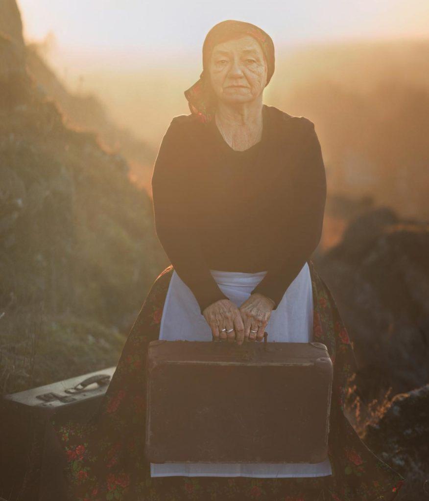 Eine alte Frau steht auf einem Berg mit altem Koffer
