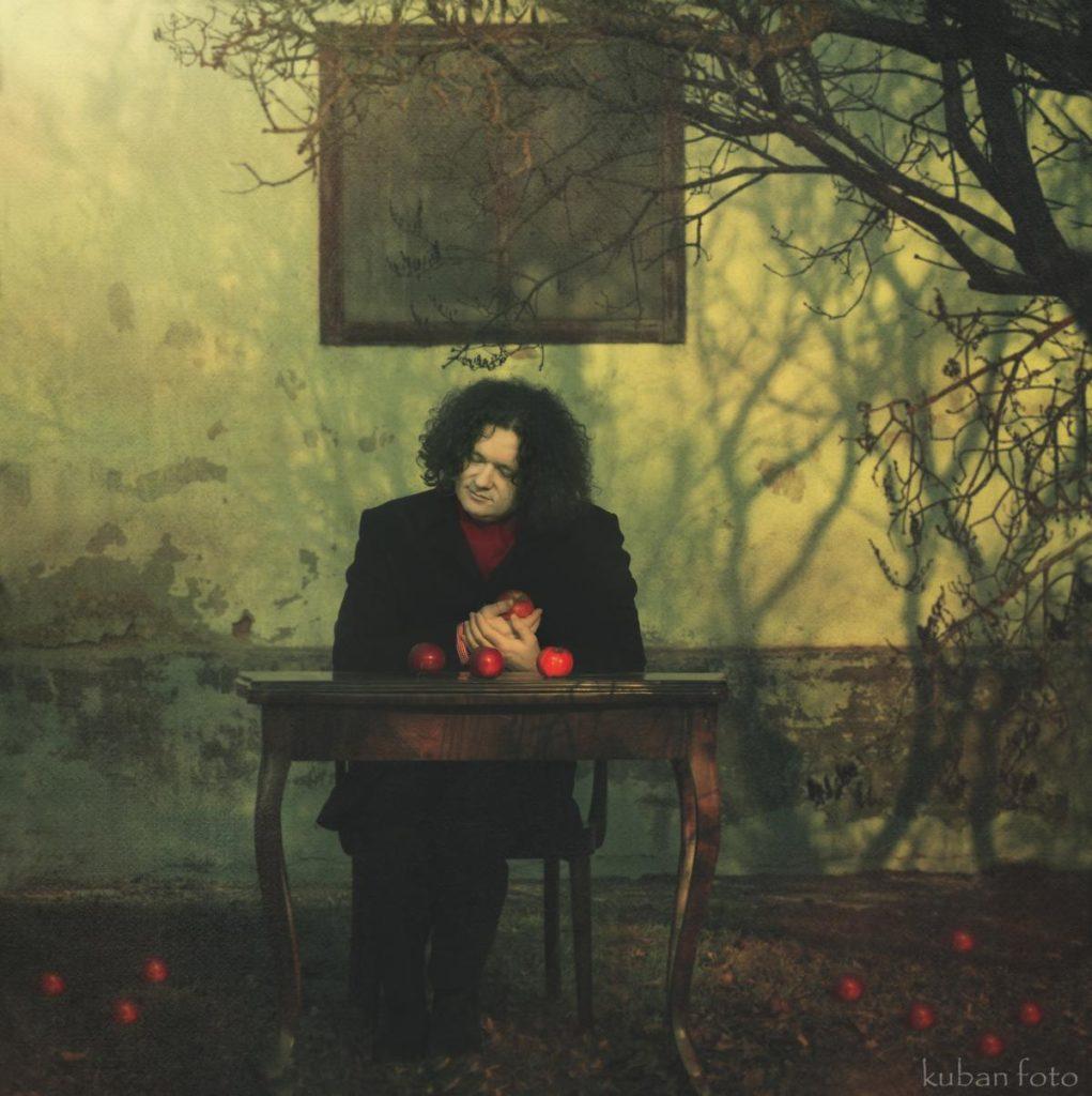 Ein Mann sitzt am Tisch mit einem Apfel in der Hand