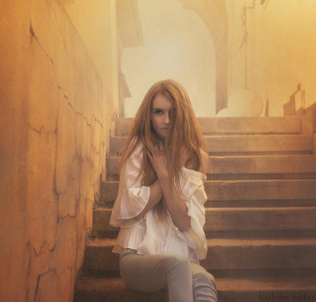 Blonde Frau sitzt mit weißer Bluse an einer Treppe in Korneuburg