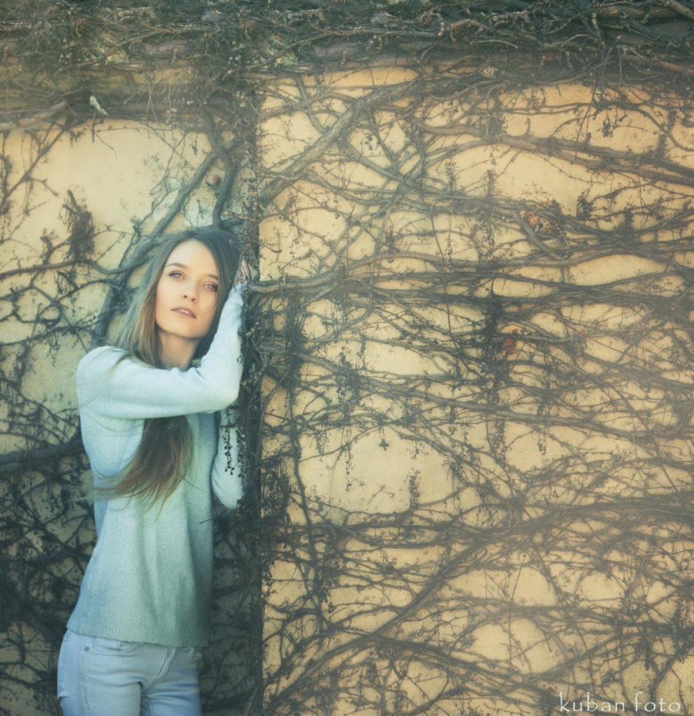 Blau gekleidete junge Dame steht angelehnt an der Wand in Korneuburg