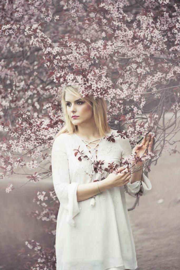 Junge Frau steht unter einem blühenden Baum
