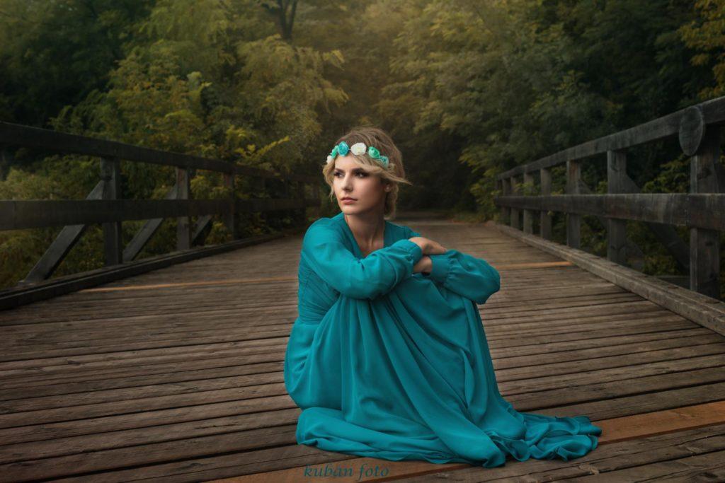 Blondes Modell sitz auf einer Brücke im Ballkleid