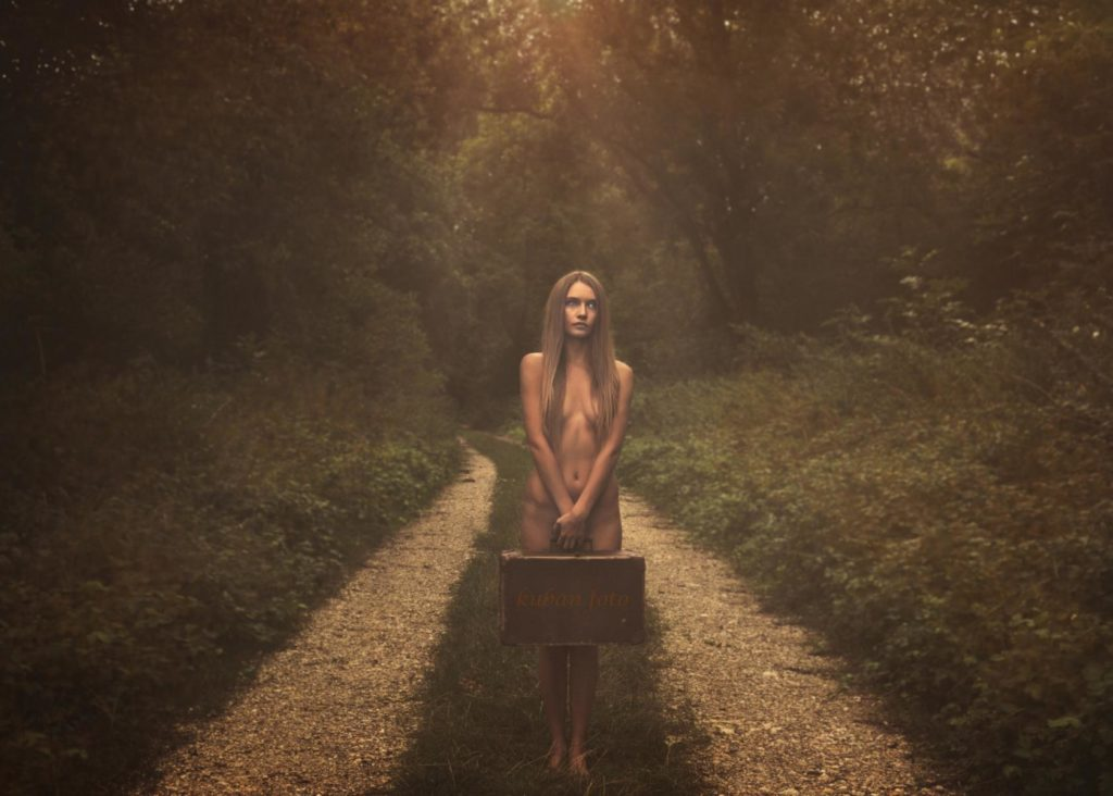 Junge Frau steht nackt auf einem Waldweg
