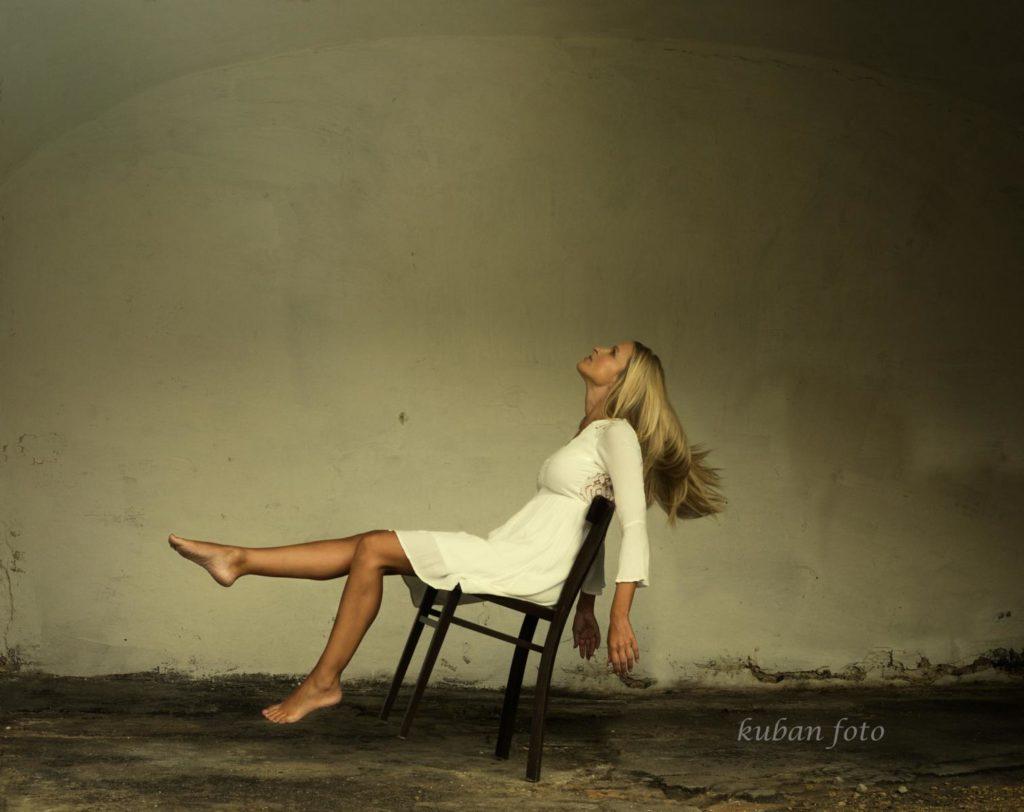 Junge Frau schwebt auf einem Stuhl