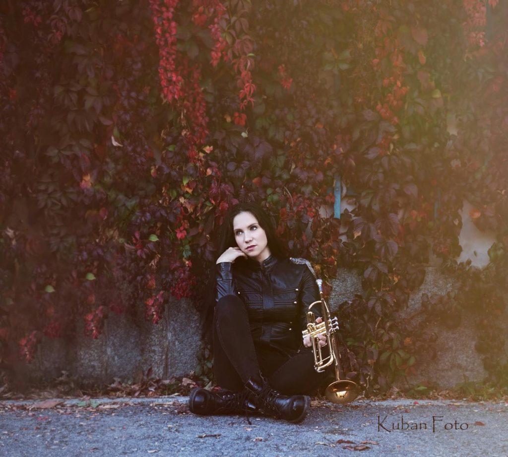 Junge Frau sitzt am Efeu mit einer Trompete