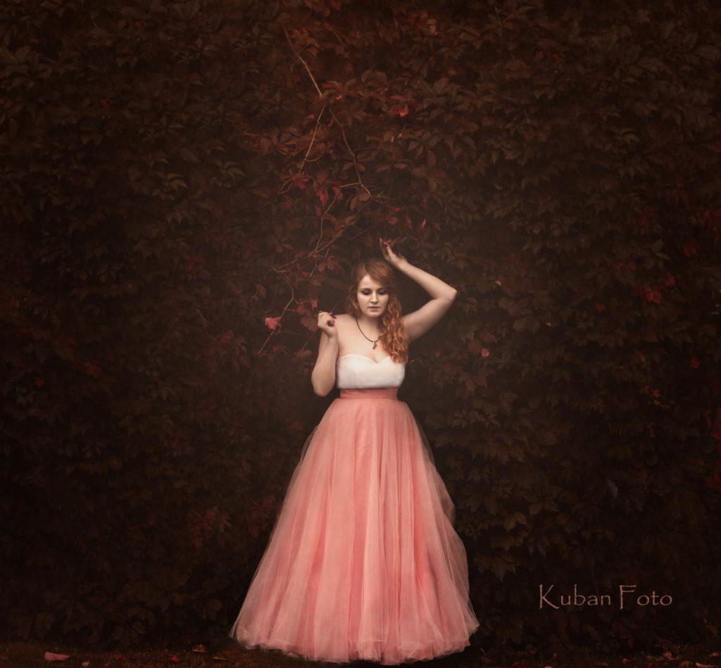 Junge Frau steht in einem Ballkleid unter Efeu