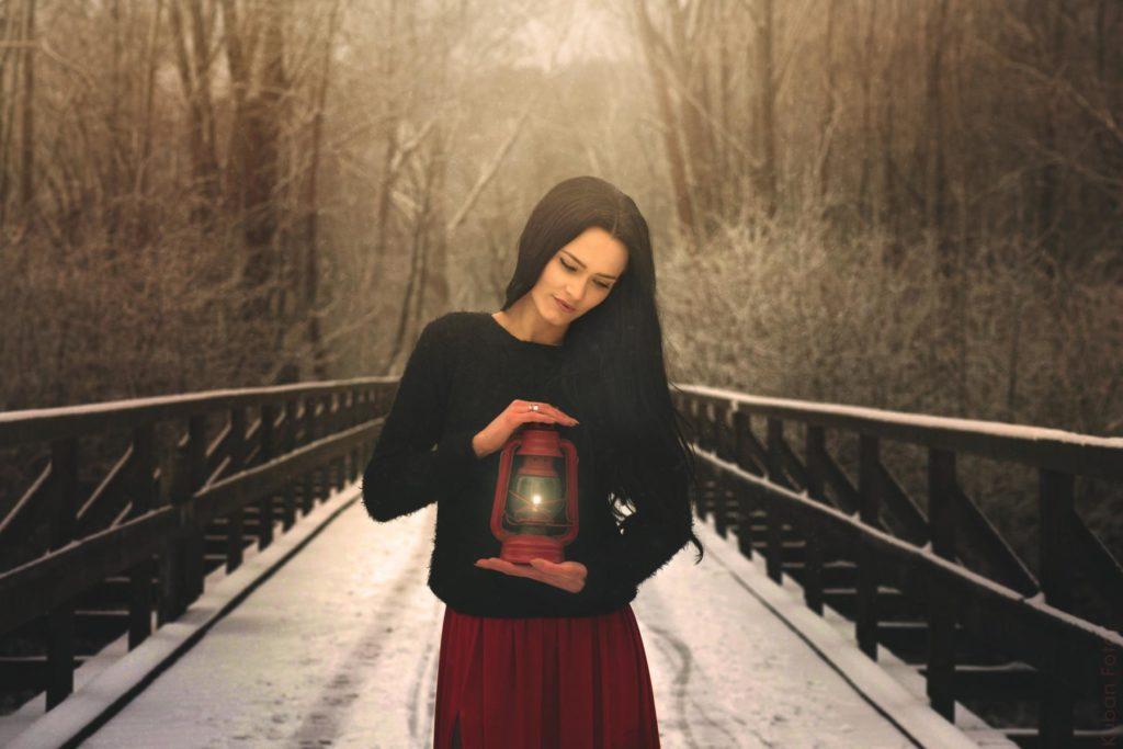 Eine junge Frau wärmt sich im Winter mit einer Lampe